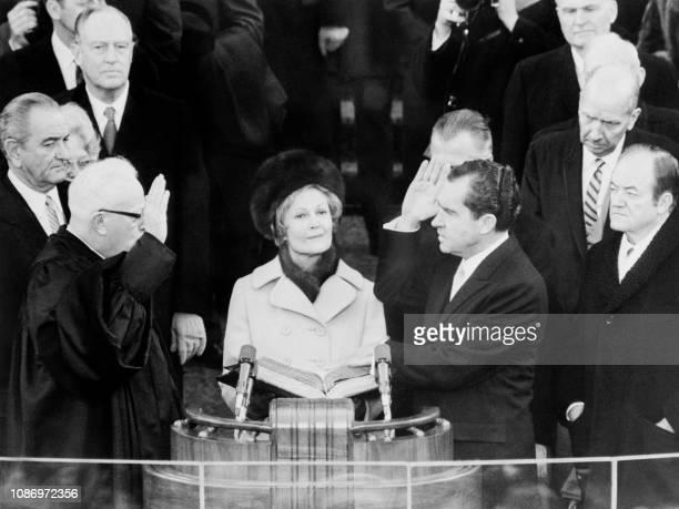 Le Président des EtatsUnis d'Amérique Richard Nixon prête serment devant Earl Warren le 20 janvier 1969 à Washington sous les yeux de son épouse AFP...