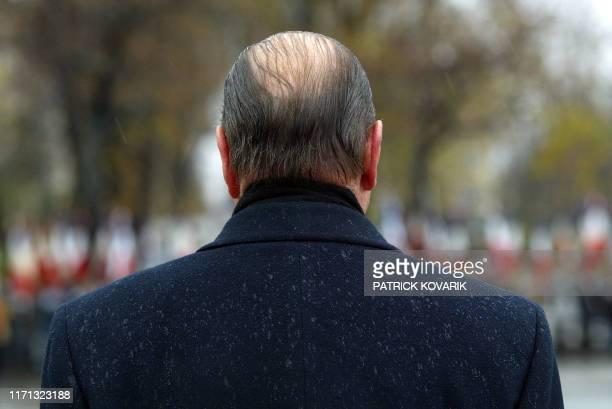 le président Jacques Chirac assiste sous la pluie le 05 décembre 2002 quai Branly près de la Tour Eiffel à Paris à l'inauguration d'un mémorial...