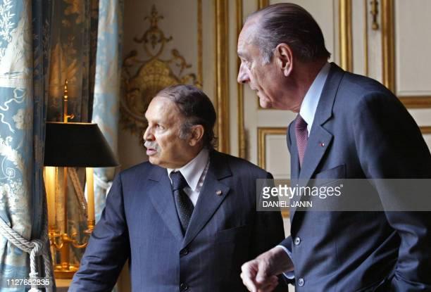le président Jacques Chirac et son homologue algérien Abdelaziz Bouteflika regardent par une fenêtre le 04 juin 2003 au Palais de l'Elysée à paris...