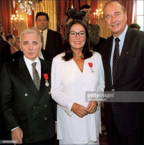 le président Jacques Chirac pose avec la chanteuse Nana Mouskouri et avec l'auteur compositeur interprète Charles Aznavour après leur avoir remis...