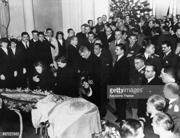 Le Président Perón se tient devant le cercueil où se trouve la dépouille de sa femme Evita pendant que la foule d'anonymes viennent se recueillirau...