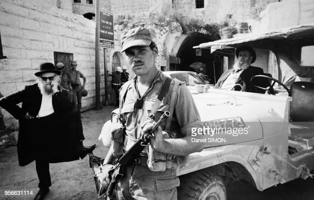 Le rabbin Moshe Levinger qui est interdit de séjour à Hébron est protégé par des soldats israëliens en octobre 1976 Hébron en Cisjordanie Israël