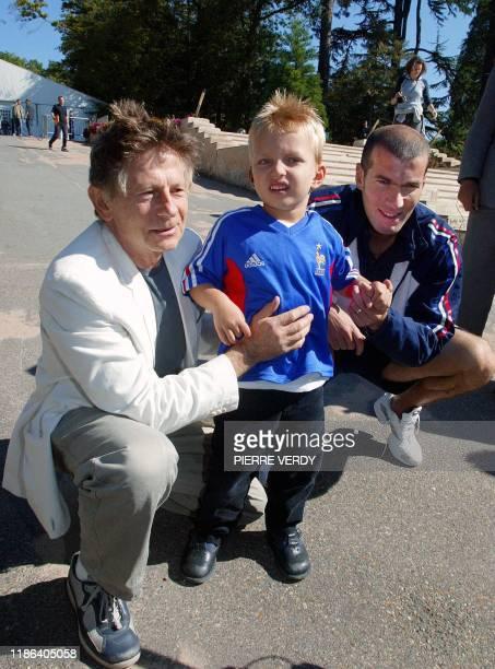 Le réalisateur français d'origine polonaise Roman Polanski et le meneur de jeu de l'équipe de France de football Zinedine Zidane posent avec Mathis,...