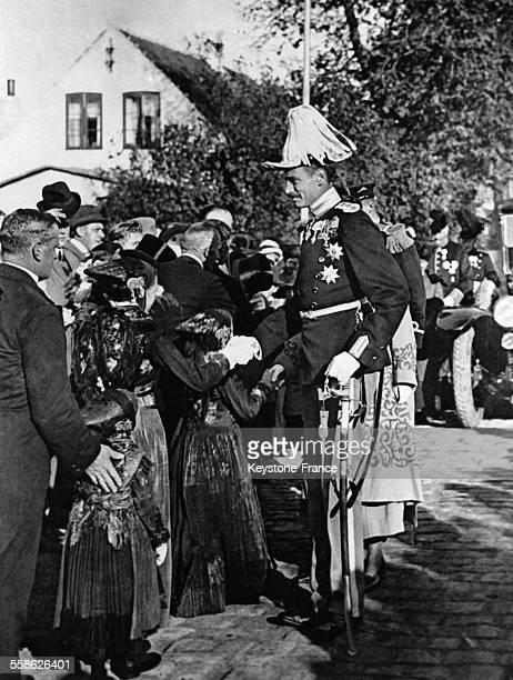 Le roi Christian X serrant les mains de jeunes filles à l'occasion du 700ème anniversaire des vieilles colonies hollandaises derrière lui la reine...