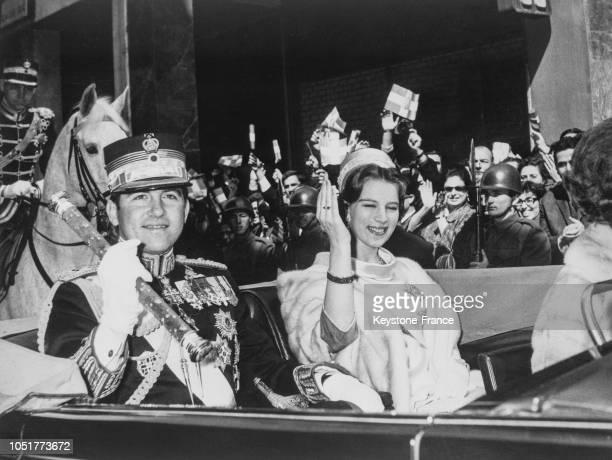 Le roi Constantin en uniforme et la reine AnneMarie en voiture acclamés par la foule à Athènes Grèce le 26 mars 1967
