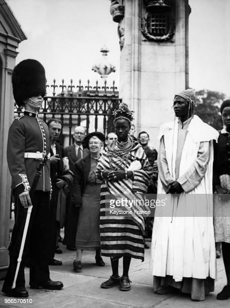 Le Roi du Bénin, Oba, et l'une des ses huit femmes, la Reine Oham Akenzua observent un garde londonien lors de leur séjour dans la capitale...