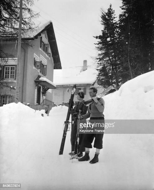 Le roi et la reine des Belges photographiés devant leur chalet 'Belvair' partant pour une promenade en ski à SaintMoritz Suisse en 1935