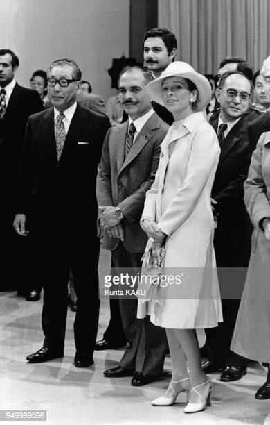 Le roi Hussein de Jordanie accompagné de son épouse Alia en manteau et chapeau blancs assistent à un spectacle de danse lors d'une réception...