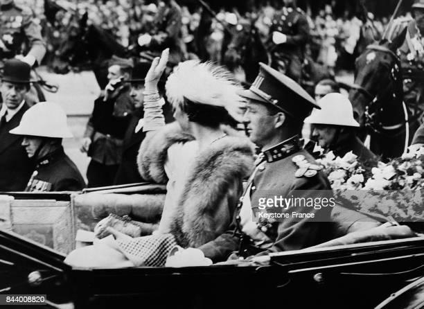 Le roi Léopold III et la reine Astrid assis dans leur voiture sont acclamés par la foule à Liège Belgique le 8 juillet 1935