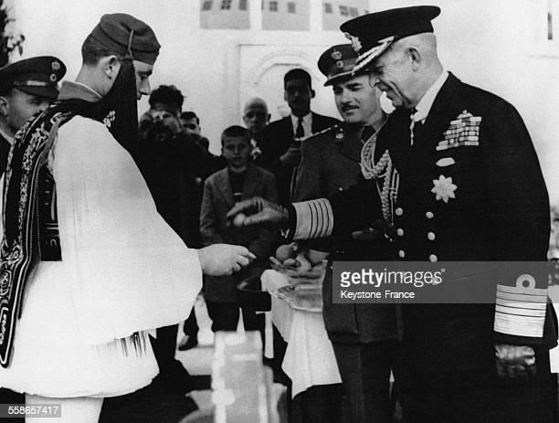 Le Roi Paul de Grèce casse un oeuf de Pâques comme le veut la tradition lors de la revue de la Garde Nationale Grecque le 16 avril 1958 à Athènes...