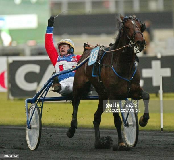 Le Romain Giampaolo Minucci, driver du cheval italien Varenne, salue les tribunes en franchissant en tête, le 27 janvier 2002 à Vincennes, la ligne...