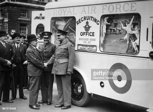 Le secrétaire d'Etat à l'Air Sir Kingsley Wood serre la main du sergent recruteur devant le bureau mobile de recrutement de l'armée positionné à...