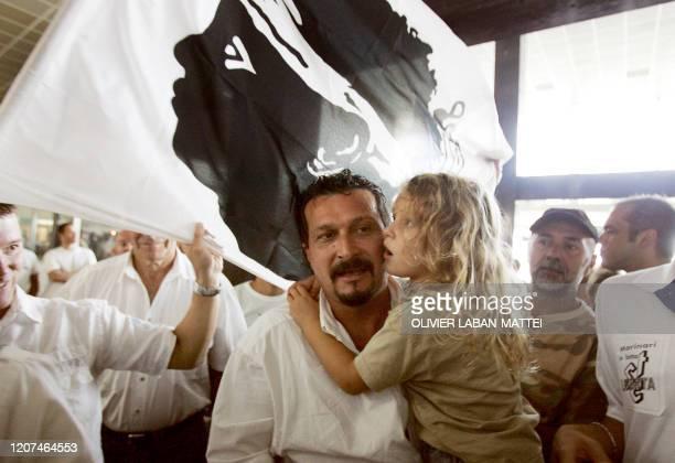 Le secrétaire national du STC marin Alain Mosconi arrive à l'aéroport de Bastia, sa fille dans ses bras, le 01 octobre 2005, sous les acclamations...