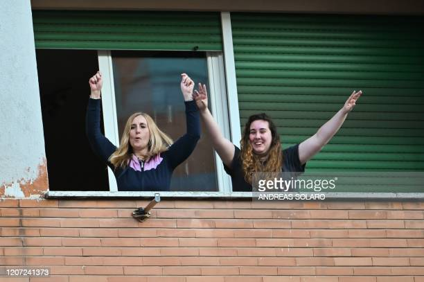 le sing wave and clap their hands during a flash mob Una canzone per l'Italia at the Magliana district in Rome on March 15 2020 Italy reacts with the...