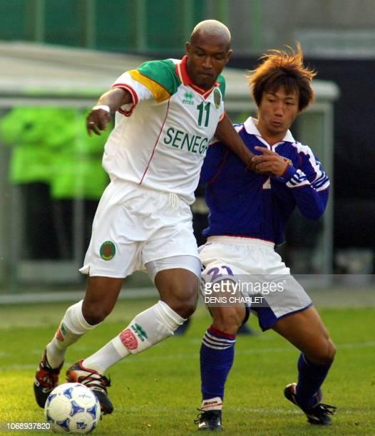 le Sénégalais El Hadji Diouf est à la lutte avec le Japonais Hato Yasuhiro le 04 octobre 2001 au stade Bollaert de Lens lors du match amical...