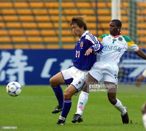 le Sénégalais Henry Camara est à la lutte avec le Japonais Hato Yasuhiro le 04 octobre 2001 au stade Bollaert de Lens lors du match amical...