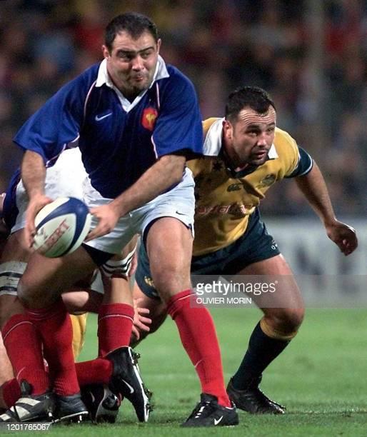 Le talonneur de l'équipe de France de rugby Raphaël Ibanez fait une passe malgré le trois quart aile australien Joe Roff le 17 novembre 2001 au stade...