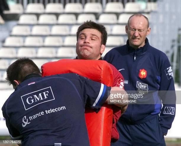 le talonneur français Fabrice Landreau est plaqué par le pilier Sylvain Marconnet sous les yeux de l'entraîneur de l'équipe de France de rugby...