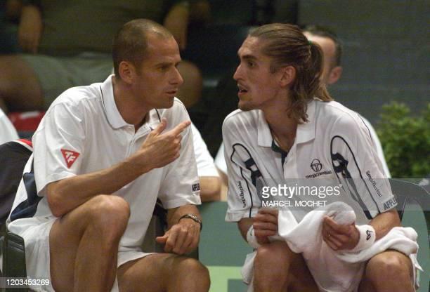 Le tennisman francais Nicolas Escudé s'entretient le 21 juillet 2000 à Rennes avec Guy Forget capitaine de l'équipe de France de tennis durant la...