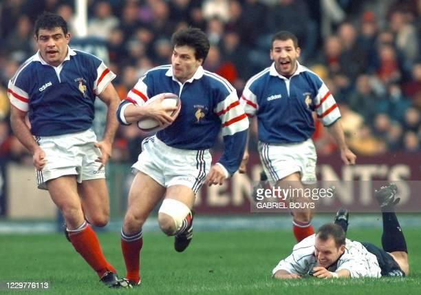 Le trois-quarts aile français Christophe Dominici déborde le trois-quarts centre écossais, Gregor Townsend, sous le regard de ses coéquipiers Raphaël...