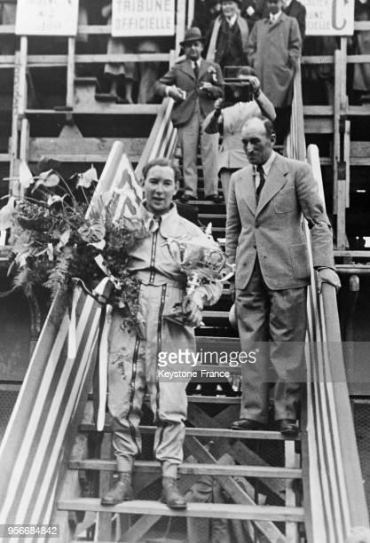 Le vainqueur Guy Moll descend de la tribune portant son trophée à Monaco en avril 1934