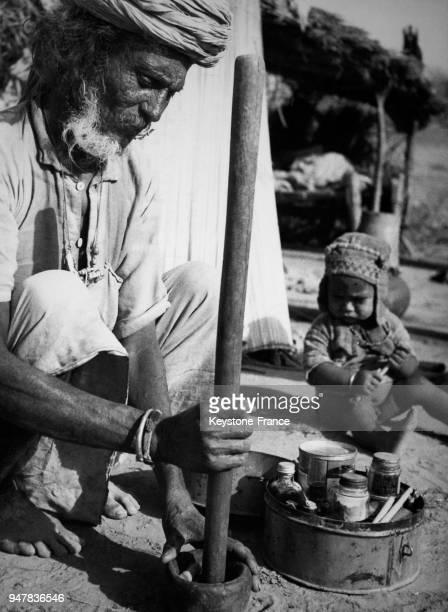 Le viel homme concocte un antidote au venin de serpent en pilant certains ingrédients naturels en Inde