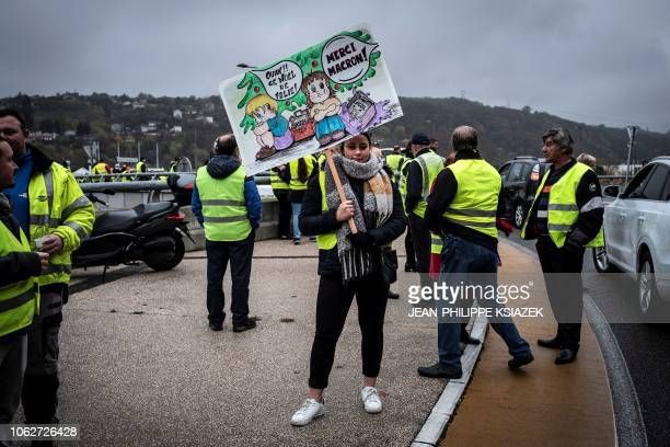 Lea Jury a student holds a banner reading 'What a bad Christmas thank you President' as she stands with other demonstrators wearing yellow vests...