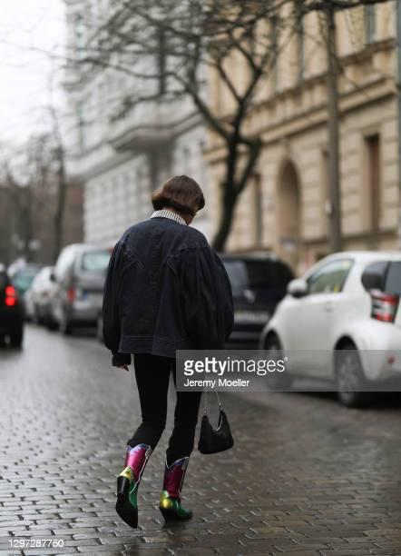 Lea Naumann wearing jeans jacket, black top, Zara pants, Prada bag and vintage boots on January 18, 2021 in Berlin, Germany.