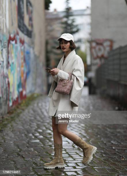 Lea Naumann wearing Nobi Talai coat, Dior bag, Zalando boots and can't decide clothing cap on January 12, 2021 in Berlin, Germany.