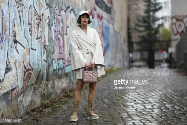 Lea Naumann wearing Nobi Talai coat, Dior bag, Zalando boots and can't decide clothing cap on January 12, 2021 in Berlin, Germany.