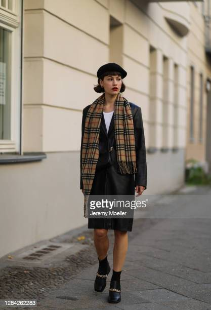 Lea Naumann wearing Prada bag, vintage black coat, Burberry scarf, H&M hat and Jeffrey Campbell boots on November 05, 2020 in Berlin, Germany.