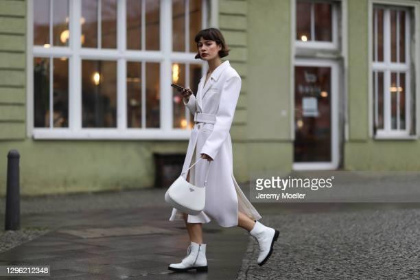 Lea Naumann wearing Prada Cleo bag, Chanel shades, Nobi Talai beige coat and Church shoes on January 12, 2021 in Berlin, Germany.
