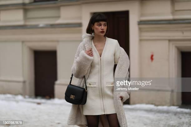 Lea Naumann wearing Sandro beige coat and dress, Falke tights, Otiumberg gold earrings, Bally black leather bag on February 15, 2021 in Berlin,...