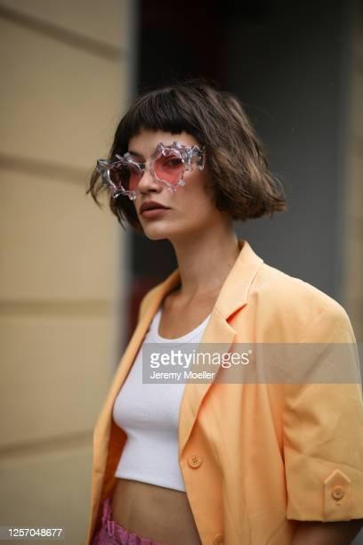 Lea Neumann wearing Komono shades, Stine Goya pants, vintage orange blazer, Urban Outfitters top on July 15, 2020 in Berlin, Germany.