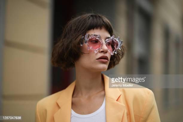 Lea Neumann wearing Komono shades, vintage orange blazer and Urban Outfitters top on July 15, 2020 in Berlin, Germany.