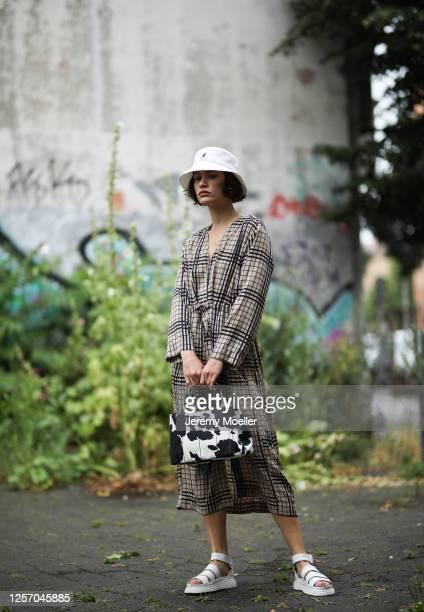 Lea Neumann wearing Prada bag, Weekday dress, Dr Martens sandals and Kangol bucket hat on July 15, 2020 in Berlin, Germany.