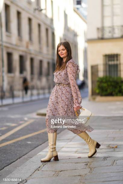Lea Platz wears silver earrings, a pink white and camel flower pattern Loavies ruffled long dress, a brown laces and silver rhinestones belt, gold...