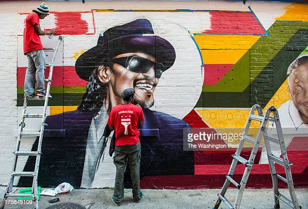 Lead Artist Aniekan Udofia center with the help of apprentice Joseph Patino left create a mural on the side of Ben's Chili Bowl featuring noted...