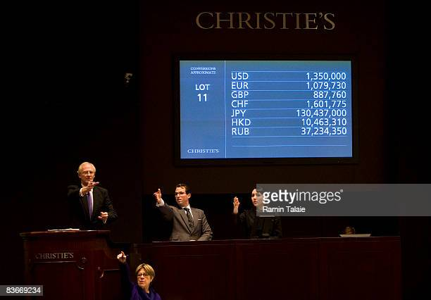Lead auctioneer Christopher Burge takes a bid on an art piece during a postwar and contemporary art sale which includes a collection owned by Richard...