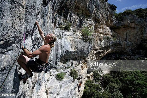 Lead climber on a rock face above a green valley in summer