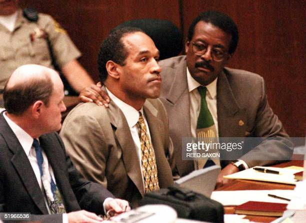 Lead defense attorney Johnnie Cochran puts his arm on OJ Simpson's shoulder after Simpson told Judge Lance Ito 22 September 1995 in Los Angeles CA...