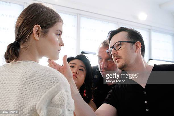 Lead makeup artist Kabuki applies makeup to a model backstage at the Ohne Titel fashion show during MADE Fashion Week Spring 2015 at Milk Studios on...