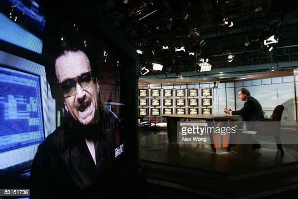 U2 lead singer Bono is seen on a TV monitor during a remote interview by moderator Tim Russert on NBC's 'Meet the Press' June 26 2005 during a taping...