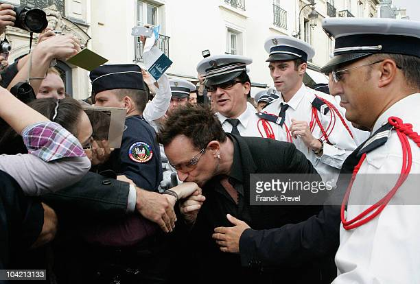 Lead singer Bono of Irish rock band U2 kisses hand of a fan after he leaves the Elysee Palace on September 17 2010 in Paris France