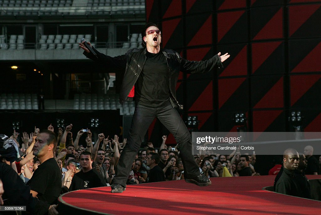 Lead singer Bono performs on stage in front of a packed house during the U2 'Vertigo' World Tour concert at Stade de France.