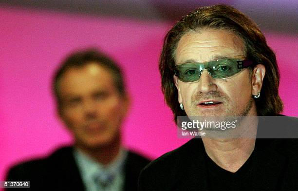 U2 lead singer Bono speaks as Britain's Prime Minister Tony Blair looks on during the fourth day of the Labour Party Annual Conference on September...