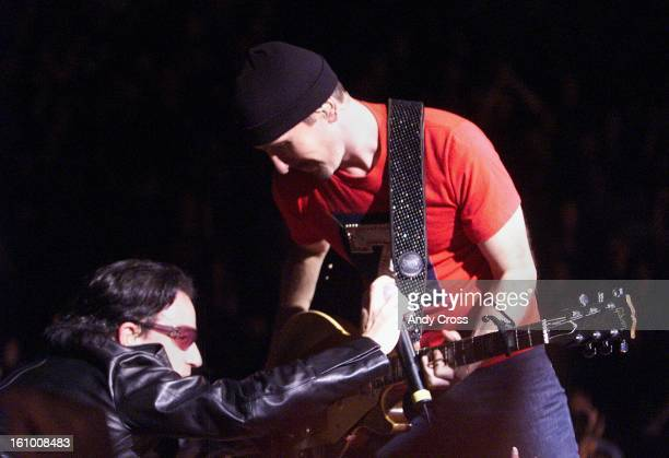 U2 lead singer Bono uses his microphone as a slide with guitarist 'The Edge' during their concert at Pepsi Center Friday evening