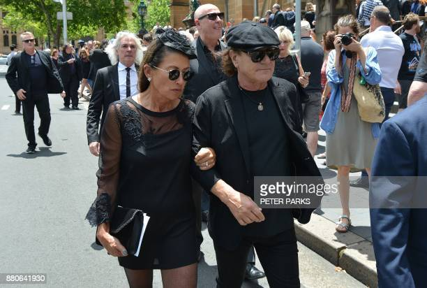 AC/DC lead singer Brian Johnson and his wife Brenda walk in front of AC/DC bassist Cliff Williams as they leave St Mary's Cathedral after the funeral...