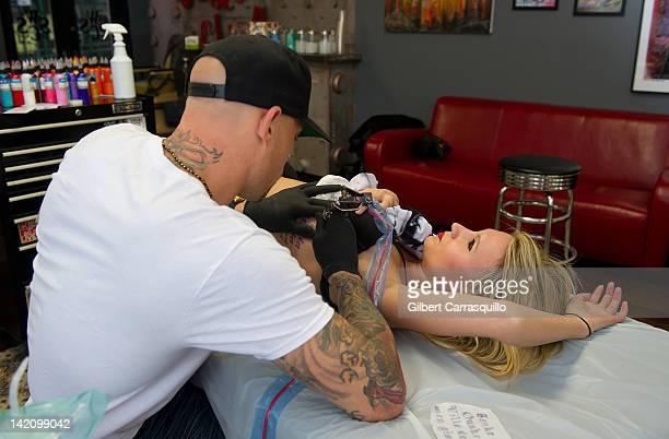 Lead singer Camilla Romestrand of the UK rock band Eddie The Gun gets tattooed by tattoo artist Ami James to promote the release of the new digital...