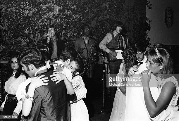 Lead singer Dennis Yost saxophone player English White and the bass player of the rock and roll band 'Classics IV' perform at a yuppie prom in circa...
